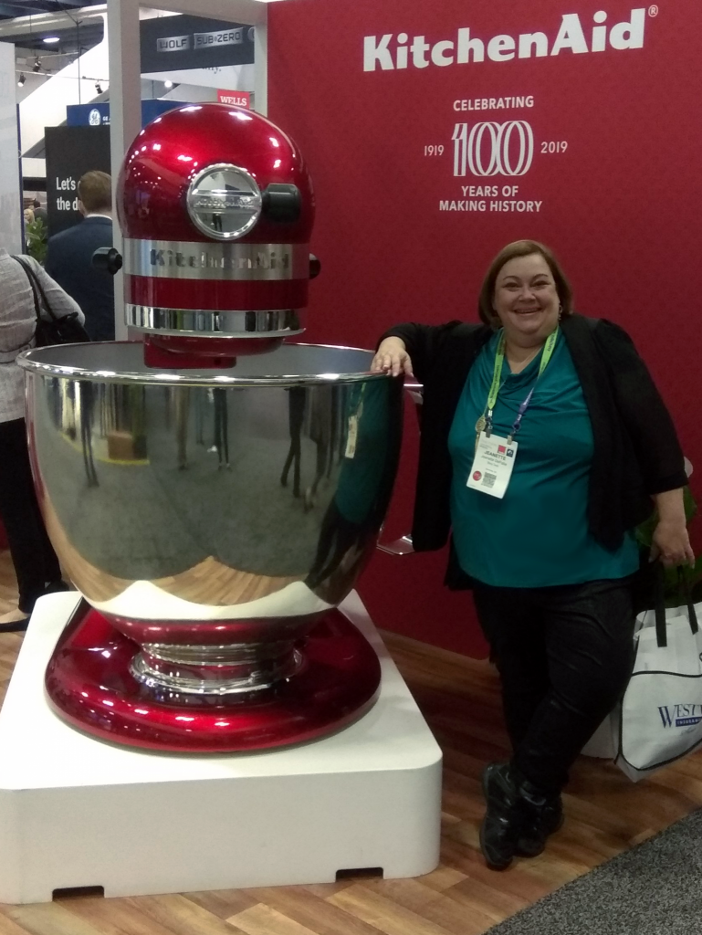 Jeanette stands next to a giant KitchenAid mixer at a trade show.